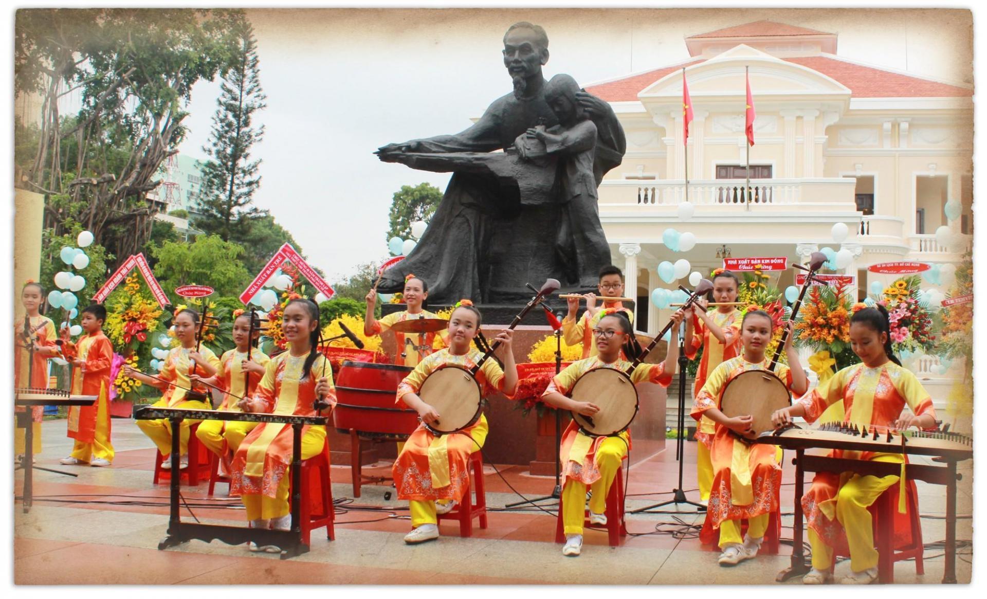 Đội văn nghệ biểu diễn nhạc cụ dân tộc dưới chân tượng đài Bác Hồ với thiếu nhi trong khuôn viên Nhà Thiếu nhi TP.HCM - Ảnh: Q.L.