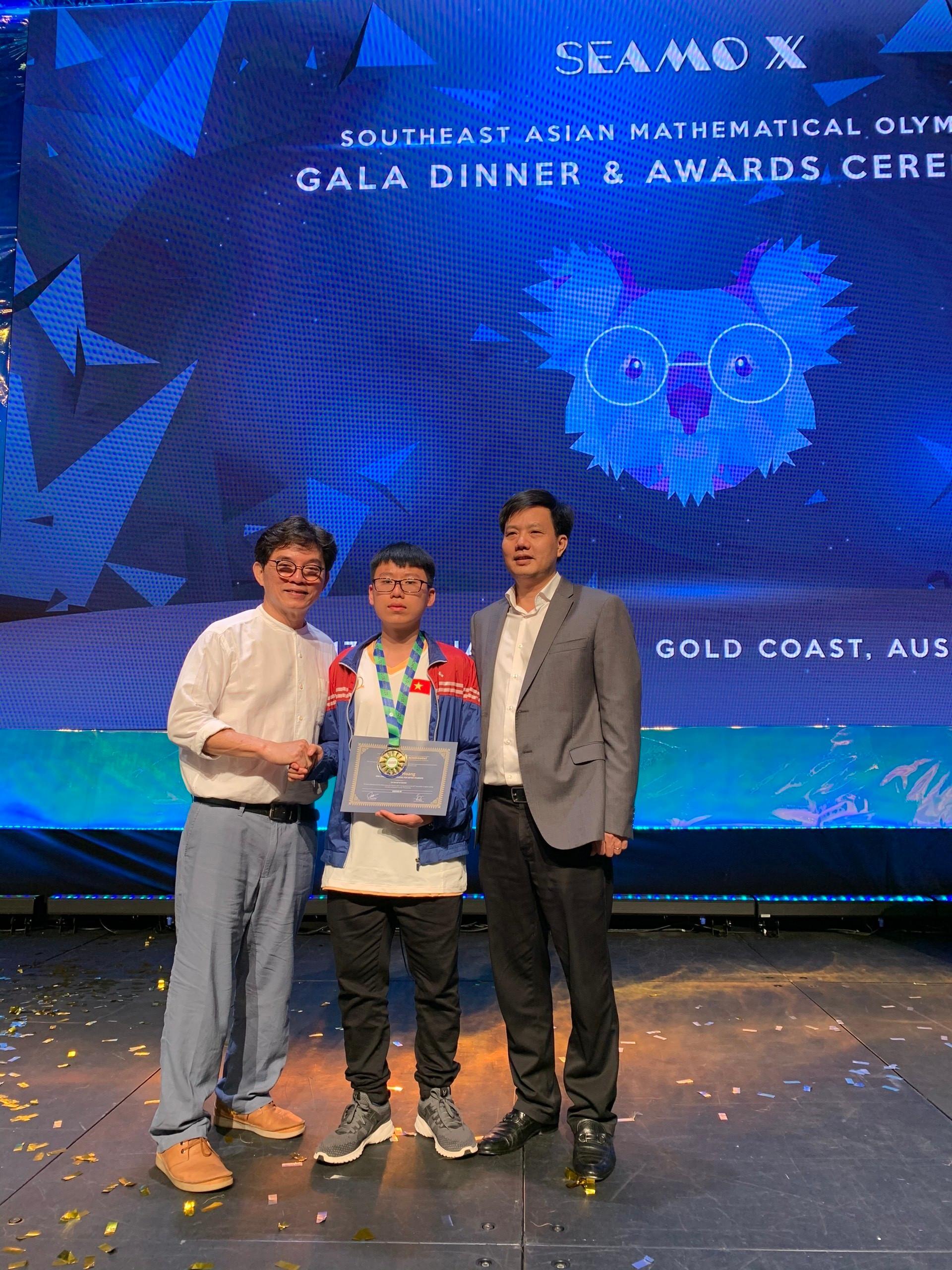 Thí sinh Lê Xuân Hoàng (giữa) cùng giáo sư Terry Chew - nhà sáng lập kỳ thi SEAMO (trái) và Tiến sĩ Nguyễn Hoàng Giang - Viện trưởng Viện nghiên cứu Khoa học Giáo dục Sáng tạo RICE (phải)