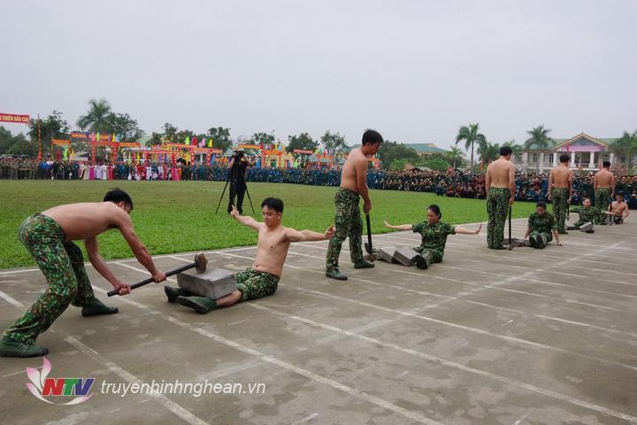 Nam và nữ nhân viên đặc nhiệm Bộ đội Biên phòng tỉnh thể hiện nội dung hai người nằm trên bàn chông và mảnh chai cho đồng đội dùng búa đập vỡ khối bê tông đặt trên bụng.