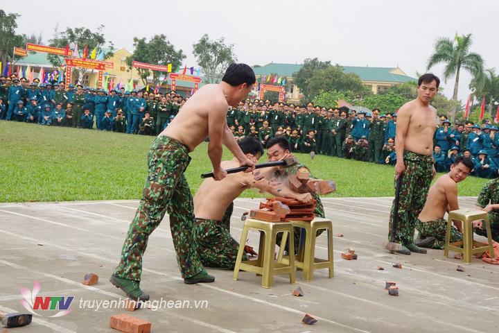 Chiến sĩ đặc nhiệm Bộ đội Biên phòng tỉnh thể hiện nội dung dùng búa đập vỡ gạch, ngói kê trên tay đồng đội