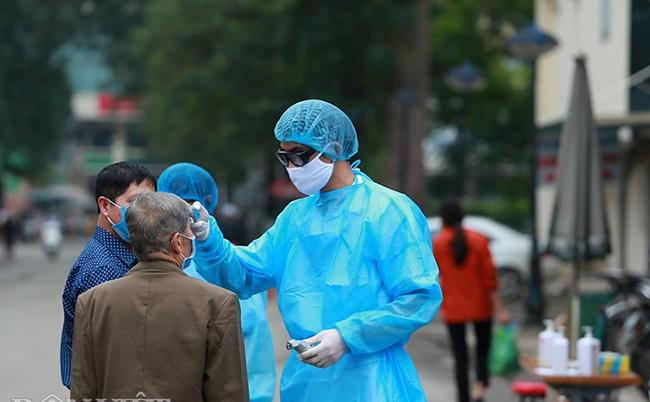 Kiểm tra thân nhiệt cho người dân đến khám tại BV Bạch Mai.