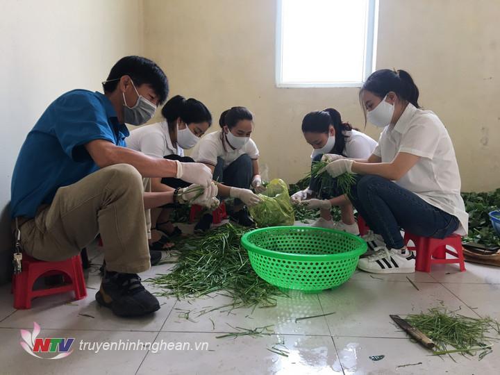 .Cán bộ Trung tâm VHTT và Truyền thông Hưng Nguyên phối hợp với các chiến sỹ hậu cần nấu ăn cho các công dân khu cách ly.