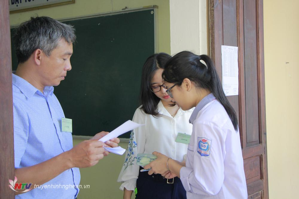 Giám thị kiểm tra giấy tờ của thí sinh trước khi gọi vào phòng thi