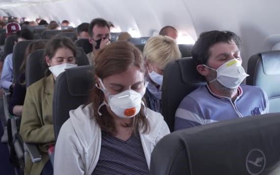 Hành khách đi máy bay phải đeo khẩu trang trong mùa dịch Covid-19. Ảnh: CNN.