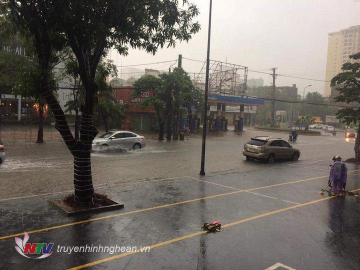 Cơn mưa lớn kéo dài khiến nhiều khu dân cư, đường phố ở TP Vinh ngập sâu trong nước. Trên là tuyến đường Lê Hồng Phong đoạn vòng xuyến giao nhâu với đường Kim Đồng.