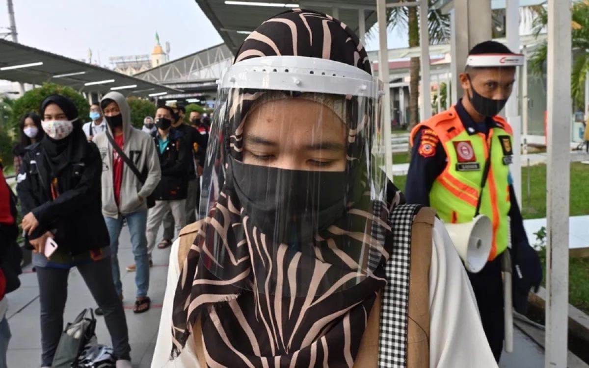 Đeo khẩu trang và tấm chắn ngừa Covid-19 ở Indonesia. Ảnh: AFP.