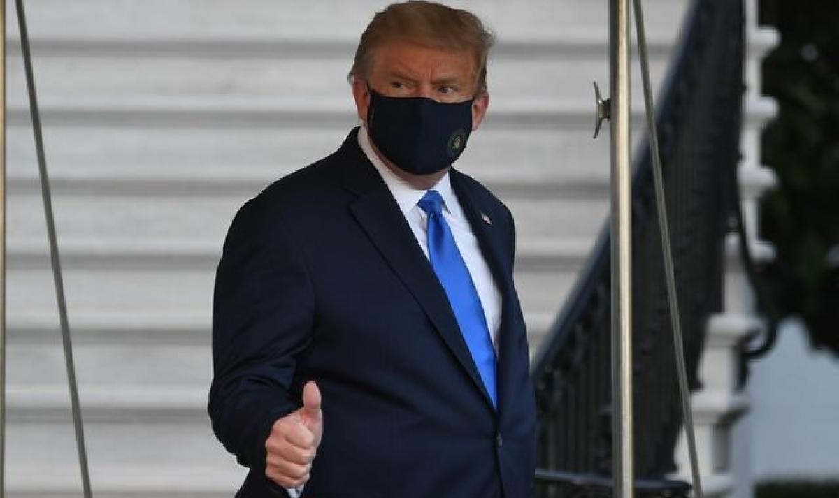Tổng thống Trump bước ra khỏi Nhà Trắng vào chiều tối 02/10 (theo giờ địa phương), giơ ngón tay cái với mọi người nhưng không nói điều gì.