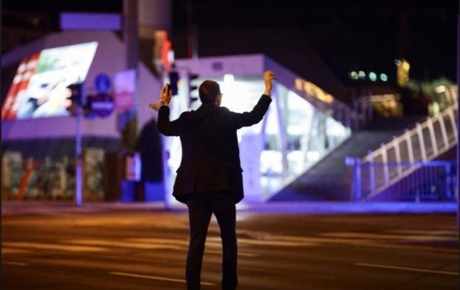 Một người đàn ông giơ tay khi cảnh sát yêu cầu kiểm tra quanh khu vực xảy ra khủng bố. (Ảnh: Reuters)