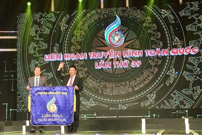 Lãnh đạo Đài Phát thanh và Truyền hình Khánh Hòa (phải) trao cờ đăng cai tổ chức Liên hoan cho đại diện Đài Phát thanh và Truyền hình Ninh Bình.