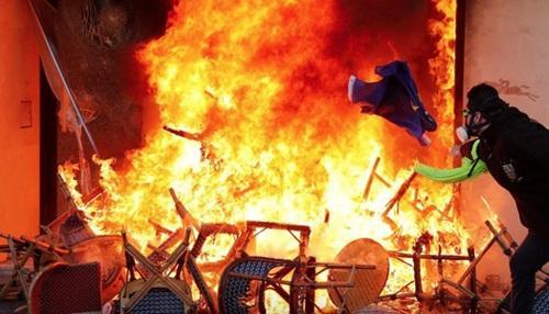 Người biểu tình ném lá cờ vào đám cháy tại một cửa hàng ở Paris hôm 16/3.