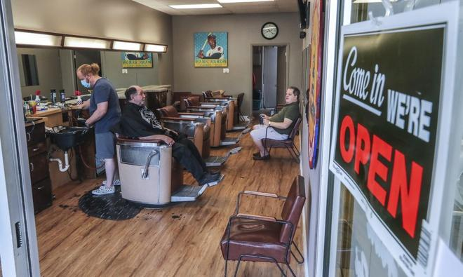 Dù tình hình dịch còn diễn biến phức tạp, một số bang như Georgia ở Mỹ đang mở cửa dần. Ảnh chụp tại một tiệm cắt tóc ở Atlanta, Georgia, hôm 24/4. Ảnh: AP.
