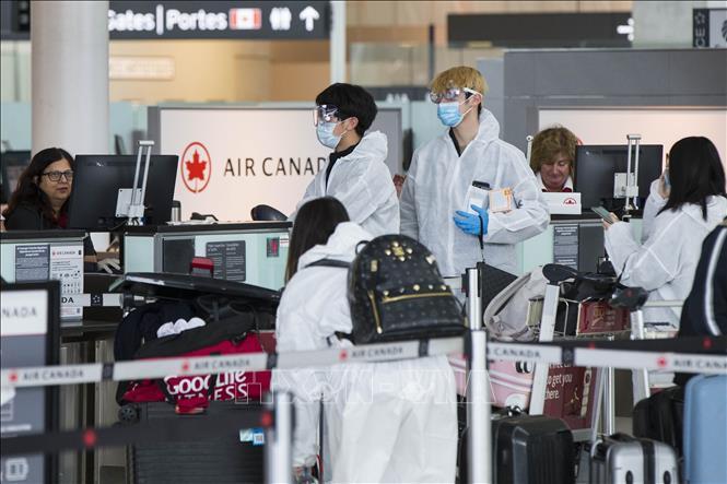 Du khách đeo khẩu trang phòng dịch COVID-19 tại sân bay quốc tế Pearson ở Toronto, Canada ngày 14/4/2020.