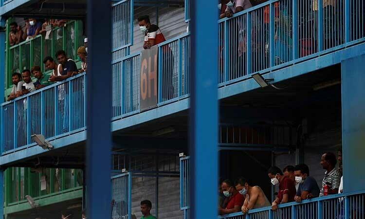 Những người lao động nhập cư trên ban công một ký túc xá ở Singapore hôm 6/4. Ảnh: Reuters.