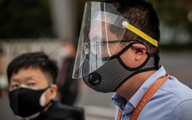 Người dân Trung Quốc đeo đồ bảo hộ phòng Covid-19 trên đường phố Bắc Kinh vào tháng 4/2020.
