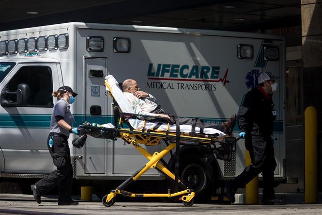 Nhân viên y tế chuyển bệnh nhân mắc COVID-19 từ xe cứu thương vào một bệnh viện ở New York, Mỹ ngày 11/4/2020.