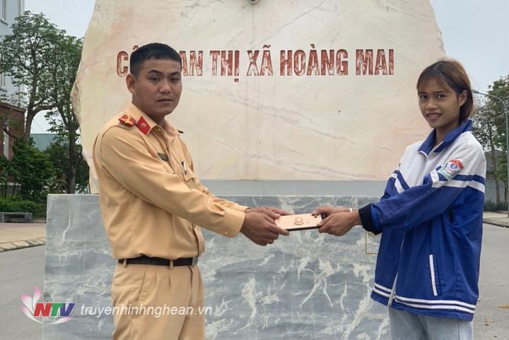 Đại diện đội CSGT Công an TX Hoàng Mai trao trả tài sản cho người dân.