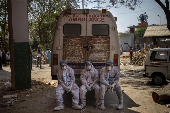 Các nhân viên y tế kiệt sức khi đưa thi thể nạn nhân đi hỏa táng. Họ ngồi xuống ngay tại cửa xe cấp cứu