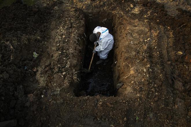 Một nhân viên mặc quần áo bảo hộ đang đào huyệt chôn nạn nhân tử vong do COVID-19 tại Gauhati, Ấn Độ.