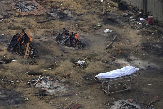 Tại trung tâm thành phố Bhopal, các lò hỏa táng đã dựng thêm giàn thiêu. Số lượng thi thể dồn dập đổ tới đã buộc các nhà hỏa táng phải bỏ qua nhiều nghi lễ cá nhân và nghi lễ của đạo Hindu cho rằng sẽ giúp linh hồn được giải thoát. Trong ảnh, một thi thể chờ được hỏa táng giữa tàn dư của các dàn hỏa thiêu.