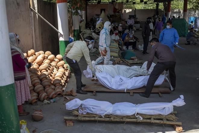 Tại các nghĩa trang thành phố như New Delhi, người dân xếp thi thể bệnh nhân COVID-19 tại lò hỏa táng.