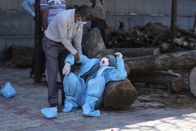 Một người nhà bệnh nhân COVID-19 suy sụp trong lễ hỏa táng tại Jammu, Ấn Độ.