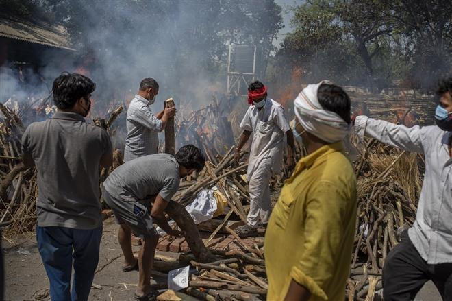 Gia đình bệnh nhân COVID-19 chuẩn bị củi lửa để hỏa táng cho người thân qua đời tại New Delhi