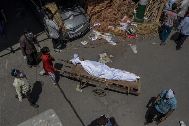 Một người đàn ông vận chuyển thi thể bệnh nhân COVID-19 trên một chiếc xe đẩy tay đến một bãi đất có lò hỏa táng.
