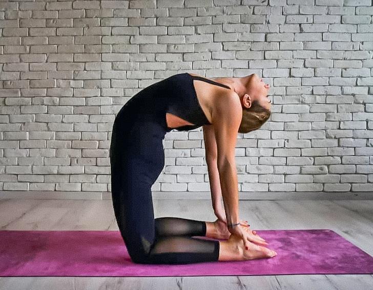 Tư thế lạc đà: Bạn quỳ trên sàn, mở rộng hai đầu gối ngang hông và để đùi vuông góc với sàn. Ngửa người ra sau, đặt 2 tay lên 2 gót chân và giữ tư thế trong 30-60 giây.