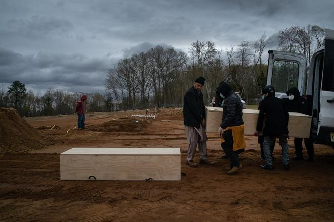 Người thân chôn cất một bệnh nhân tử vong vì virus corona ở New Jersey. Ảnh: NYT.
