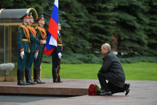 Tổng thống Putin đặt một bó hoa hồng đỏ lên đài tưởng niệm chiến tranh ngoài điện Kremlin hôm 9/5. Ảnh: Reuters.