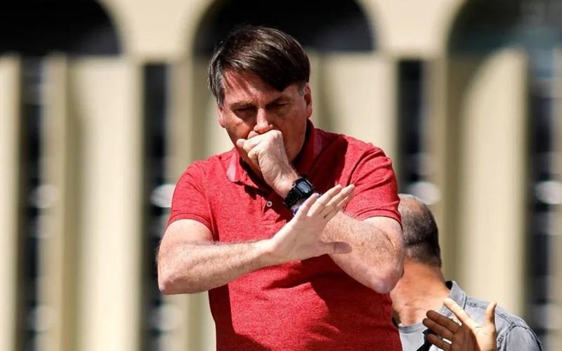 Tổng thống Brazil Bolsonaro ho khi phản đối cách ly xã hội phòng Covid-19. Ảnh: AFP.