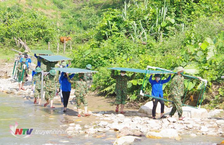 Bộ đội và đoàn viên thanh niên địa phương vượt suối vận chuyển vật liệu xây dựng chốt