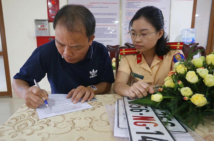Một tài xế làm thủ tục cấp đổi biển số, sang tên ở Cục Cảnh sát giao thông.
