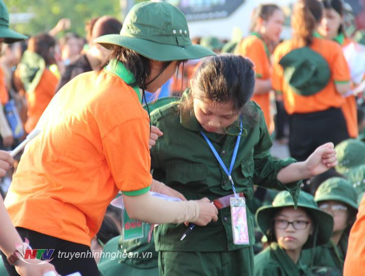 Tình nguyện viên giúp đỡ học viên chỉnh trang trang phục.