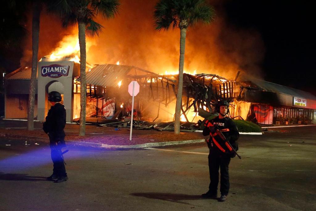 Cảnh sát canh giữ hiện trường vụ cháy trong đêm bạo loạn ở Tampa, Florida, đêm 31/5. Nhà hàng của ông Thanh Sơn ở bên phải.
