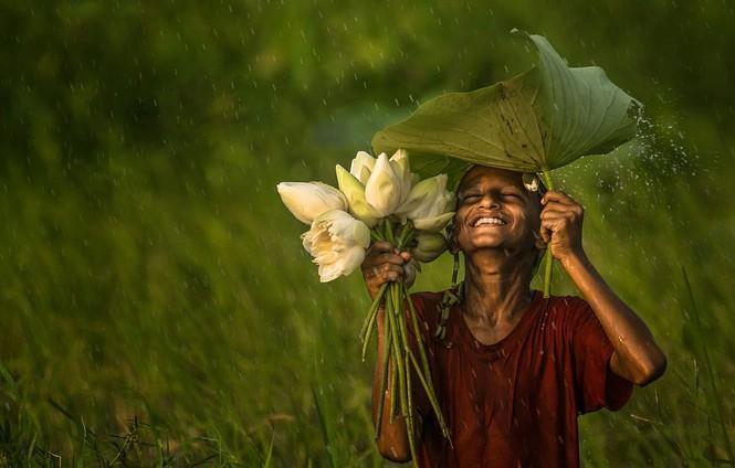 """Bức ảnh duy nhất giành chiến thắng của nhiếp ảnh gia @phOWNasaf (Bangladesh) có tên: """"Có người tận hưởng cơn mưa, nhưng có người lại khó chịu vì bị ướt"""" được chụp tại Akkelpur, Joypurhat, Bangladesh. """"Đó là một ngày nắng và tôi đã lên kế hoạch đi chụp ảnh. Tôi phát hiện ra cậu bé này đang hái hoa, và chỉ một lát sau mưa bắt đầu trút xuống. Cậu ấy nở nụ cười tươi nhất và thuần khiết nhất trên khuôn mặt khi bị ướt. Đối với tôi, hạnh phúc là một trong những kết quả của đức tin đúng đắn. Niềm tin mang lại cho bạn sự tự tin, và sự tự tin mang đến cho bạn năng lượng. Và khi bạn cảm thấy năng lượng, bạn cười một cách vô thức"""", nhiếp ảnh gia viết."""