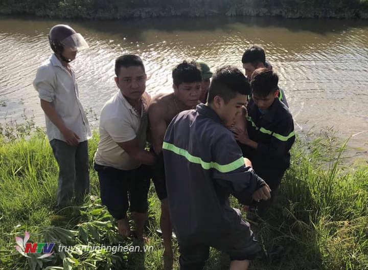 Lực lượng chức năng di chuyển thi thể nạn nhân lên bờ.