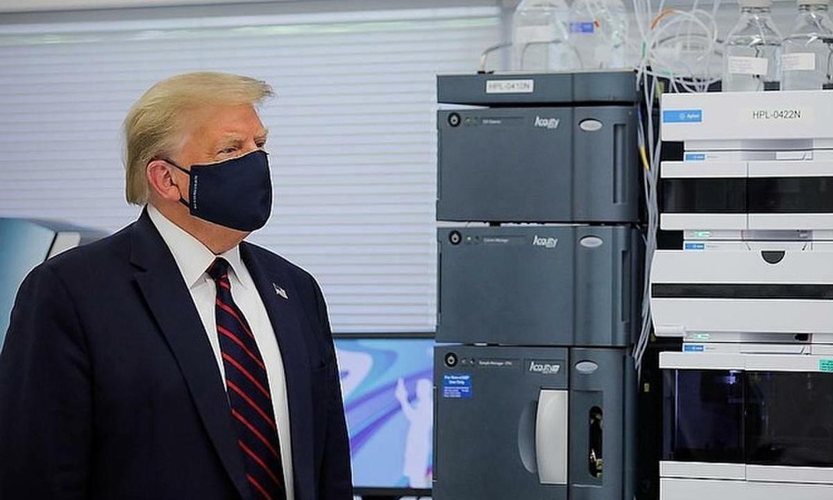 Trump đeo khẩu trang khi thăm trugn tâm vắc xin của Mỹ. Ảnh: Reuters