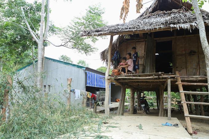 Chuồng bò xây gạch, lợp mái tôn (màu xanh) nằm bên cạnh một nhà dân đang mái tranh ở bản Văng Môn.