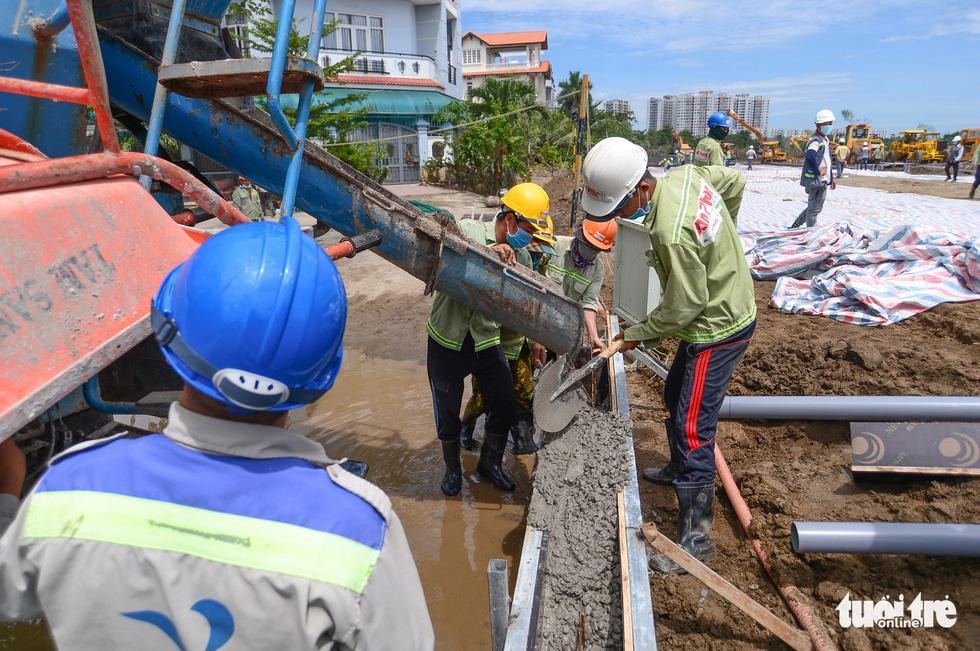 Công nhân đổ bêtông thi công hàng rào dự án