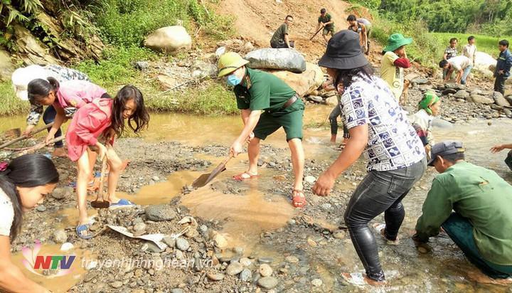 CBCS Đồn BP Na Ngoi cùng đồng bào khai thác, vận chuyển đất đá làm đường dẫn bắc cầu tạm qua suối