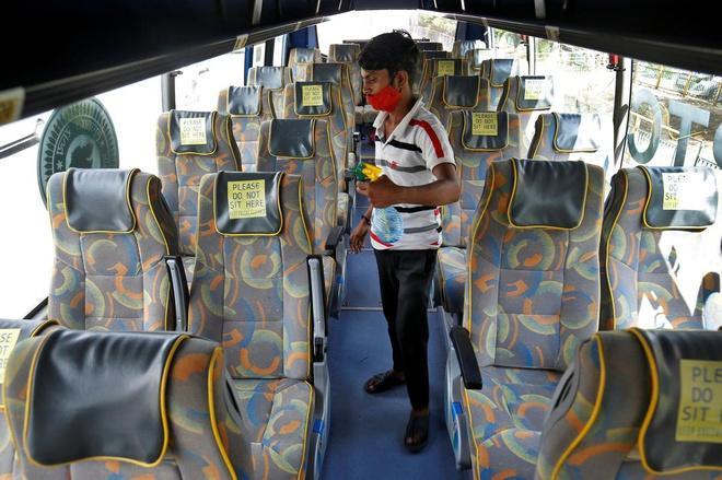 Người đàn ông đeo khẩu trang khử trùng ghế ngồi trên xe buýt sau khi chính quyền bang Gujarat cho phép xe buýt hoạt động lại. Ảnh: Reuters.