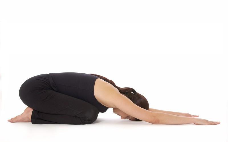 Bài 2 - Kéo giãn toàn bộ lưng: Ở tư thế ngồi trên gót, bàn chân và các ngón chân ép sát với nhau. Bạn gập đầu gối ép sát đùi với cẳng chân và hạ trán xuống đất với hai tay đưa thẳng về phía trước. Duỗi tay áp sát tai trong 30 giây.