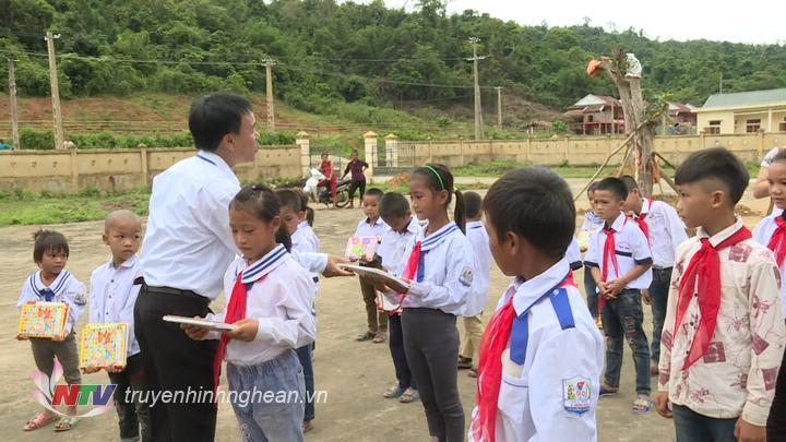 Thầy cô giáo tặng vở cho học sinh nhân dịp khai giảng.