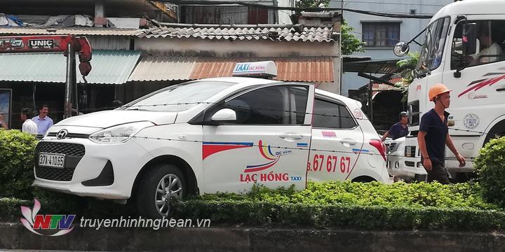 Xe taxi lao lên dải phân cách sau va chạm.