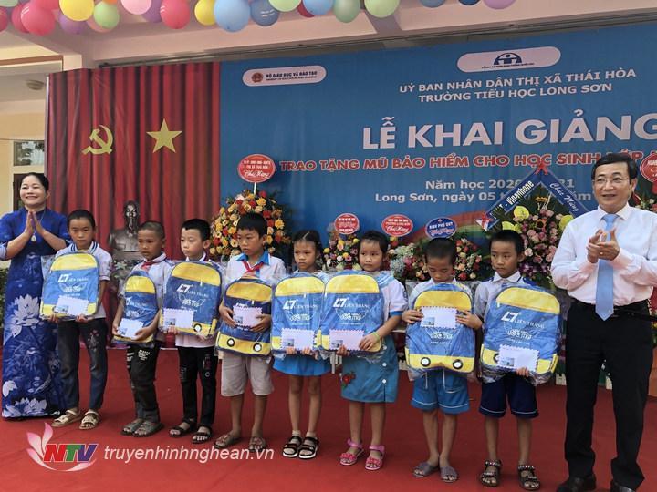 Lãnh đạo thị xã Thái Hòa tặng quà cho cáo em học sinh.
