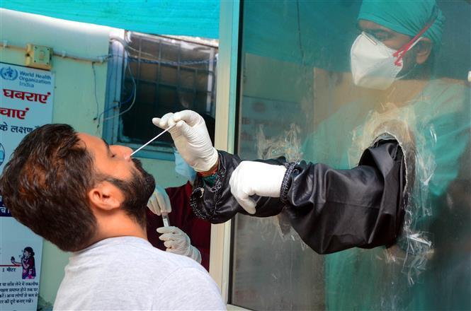 Nhân viên y tế lấy mẫu dịch xét nghiệm COVID-19 cho người dân tại Haridwar, Ấn Độ, ngày 19/9/2020.