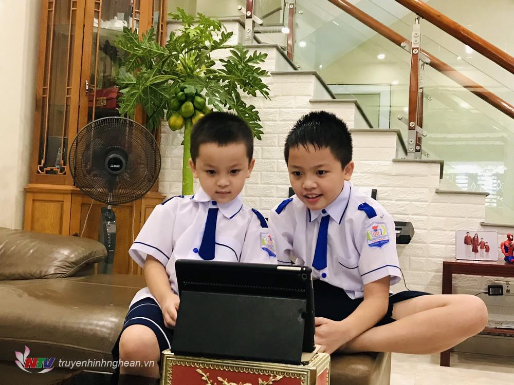 Em Hoàng Gia Hưng học sinh lớp 4H cùng em trai Hoàng Khánh Toàn lớp 1H trường Tiểu học Thị Trấn cùng xem lễ khai giảng năm học mới.