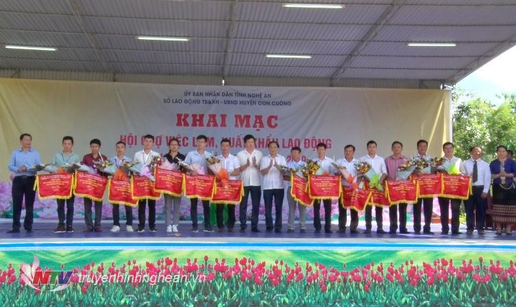 Lãnh đạo Sở LĐ-TB&XH và lãnh đạo huyện Con Cuông tặng hoa cho các đơn vị, doanh nghiệp tham gia Hội chợ.