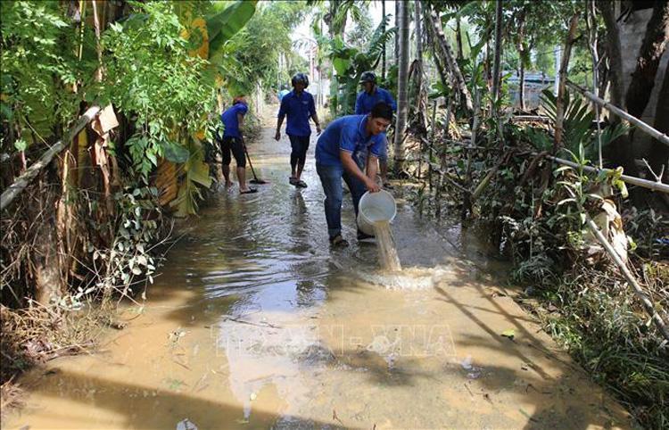 Lực lượng đoàn viên thanh niên hỗ trợ người dân dọn dẹp sau bão.